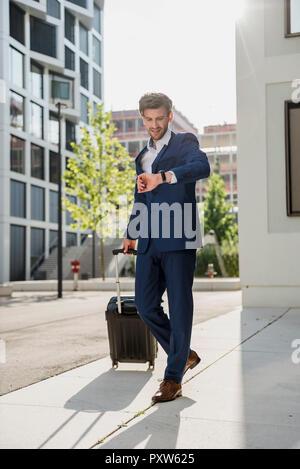 Geschäftsmann mit Gepäck in der Stadt auf die Bewegung, das mal prüfen. - Stockfoto