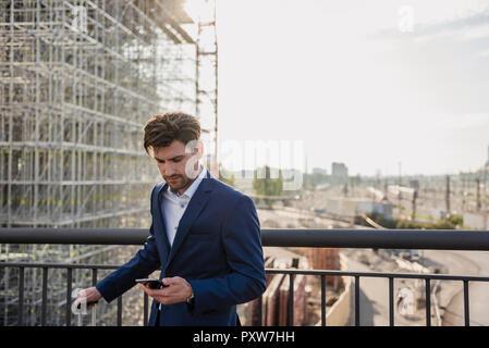 Geschäftsmann auf der Brücke in der Stadt mit Handy - Stockfoto