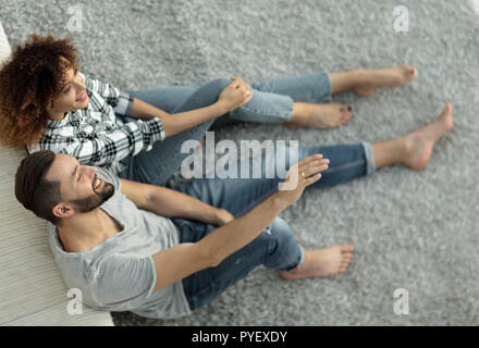 Frisch vermählte Paar sitzt auf einem Teppich in einem neuen Wohnzimmer - Stockfoto