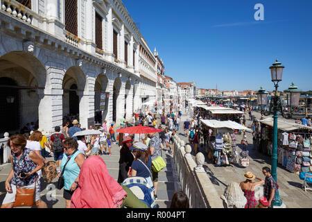 Venedig, Italien - 13 AUGUST 2017: Menschen und Touristen in Venedig zu Fuß mit Sonnenschirmen unter der Sonne in der Nähe von San Marco Platz an einem sonnigen Sommertag in Ita - Stockfoto