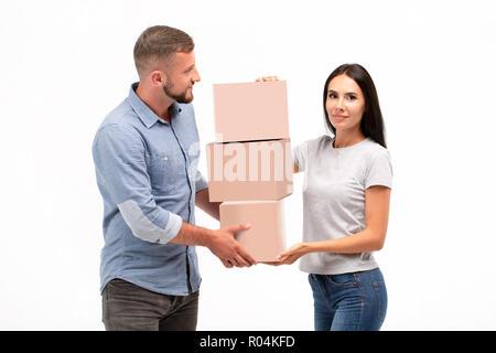 Attraktive junge Paar Durchführung Umzugskisten auf weißem Hintergrund - Stockfoto