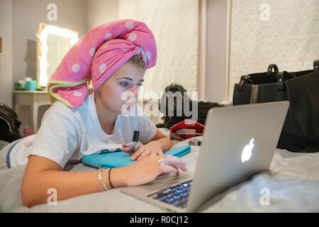 Ein junges Mädchen malt Ihre Nägel in Ihr Haar mit einem rosa Handtuch auf den Kopf gewaschen, immer bereit, zu einer Partei, während Ihr Hund schaut auf Go - Stockfoto