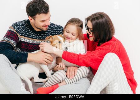 Foto von freundlichen Familie sich umarmen und ihr Hund flacher, Spaß haben, stellen gemeinsam gegen den weißen Hintergrund. Kleine weibliche Kind, ihr Vater, m - Stockfoto