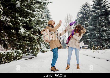 Datum des jungen Paares im Winter. Jungen kaukasischen Mann mit Bart und langen Haaren Aprilscherze kid snow Schneebälle mit einer Frau, winter spiele Va - Stockfoto