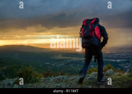 Silhouette von einen Mann auf einem Berg in Wanderausrüstung, unter Approaching Storm clouds in den Strahlen der untergehenden Sonne - Stockfoto