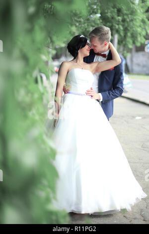 Braut und Bräutigam einander umarmen, stehend auf einer Straße der Stadt - Stockfoto
