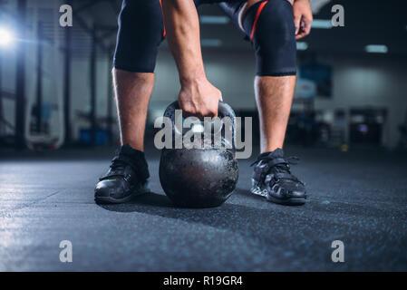 Starke männliche Athlet bereitet sich auf die Übung mit kettlebell anheben. Weightlifting Workout in Sport oder Fitness Club, Lifter Gewicht auf die Ausbildung in der Turnhalle - Stockfoto