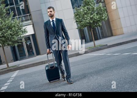 Junge Unternehmer mit einem Koffer auf Rädern Spaziergänge auf der leeren Straße - Stockfoto
