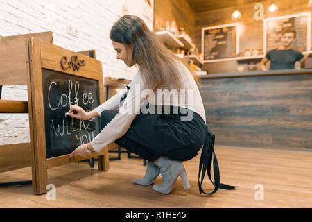 Kaffee mit Ihnen, schreibt in Kreide auf Tafel der jungen weiblichen Besitzer des Coffee House - Stockfoto