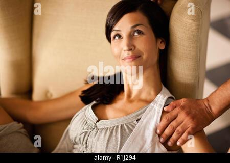Mitte der erwachsenen Frau im Sessel mit einem Mann die Hand auf die Schulter. - Stockfoto