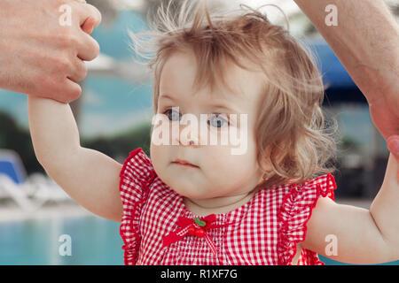 Die adorable Baby girl Holding Vater Hände beim Lernen im Freien zu laufen. Schwimmbad Hintergrund. Baby suchen Nach oben - Stockfoto
