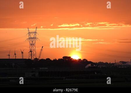 Schönen Sonnenuntergang mit einem orangefarbenen Himmel. Strommast, Stromleitungen und Windenergieanlagen sind gegen den Abendhimmel. - Stockfoto