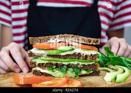 Köstliche avocado Sandwich auf Schneidebrett. Frisches Gemüse Sandwich mit rohen Zutaten, Nahaufnahme - Stockfoto