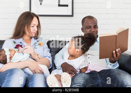 Eltern lesen Sie ein Buch für Kinder sitzen auf der Couch. Happy multiethnischen Familie. Die Werte der Familie - Stockfoto
