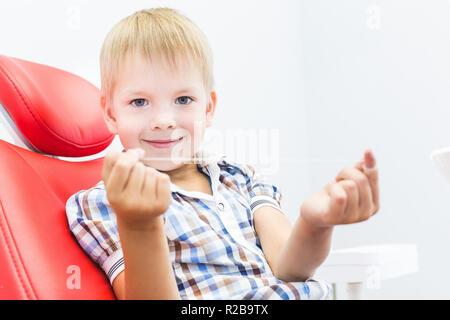 Zahnmedizinische Klinik. Rezeption, die Untersuchung des Patienten. Zähne kümmern. Ein kleiner Junge mit Zahnseide sitzt in einem behandlungsstuhl. Mundhygiene Konzept - Stockfoto