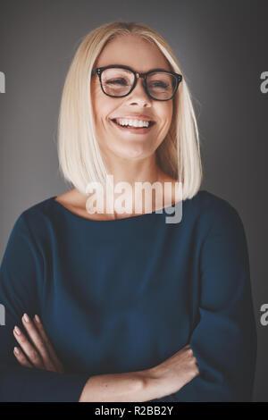 Lächelnden jungen Geschäftsfrau Brillen stehen mit ihren Armen vor grauem Hintergrund gekreuzt - Stockfoto