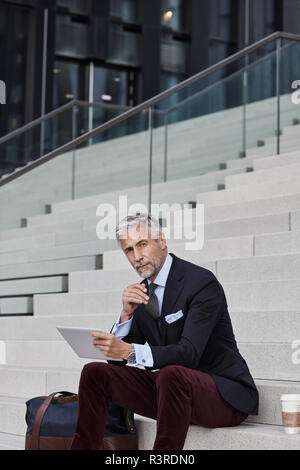 Portrait von modischen Geschäftsmann mit Reisetasche, Kaffee trinken gehen und Tablet sitzen auf Treppen - Stockfoto
