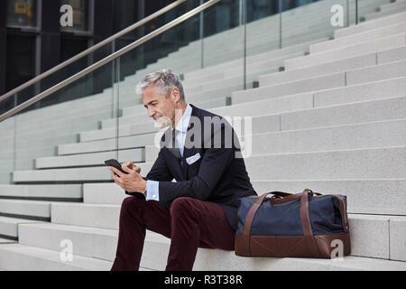 Modische Geschäftsmann mit Reisetasche sitzen auf der Treppe mit Handy - Stockfoto