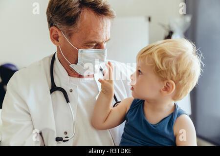 Kind auf den Schoß der Kinderarzt, durch das Tragen von schützender Maske - Stockfoto