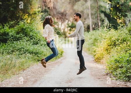 Paar springen und Lachen in der Mitte der grünen Straße - Stockfoto