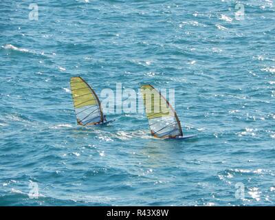 Zwei Windsurfer gehen unter der grellen Sonne in schwerer See im Meer bei hohen Geschwindigkeiten - Stockfoto
