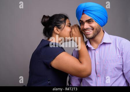 Junge glücklich indische Frau flüstert ihr lächelnd Freund - Stockfoto