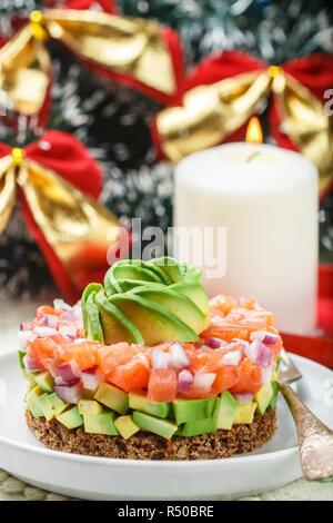 Lachstatar (Forellen) mit Avocado und rote Zwiebel auf Roggenbrot. Einstimmung auf Weihnachten und das Neue Jahr. Einen leichten Snack für Gourmets. Selektiver Fokus - Stockfoto