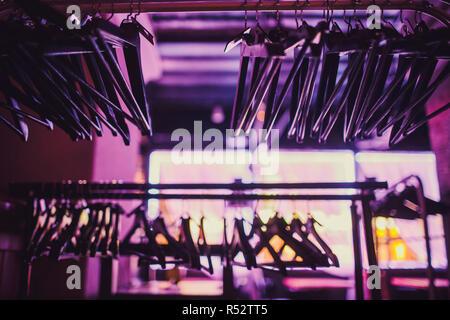Lager für leere Kleiderbügel im Schrank, hölzernen Kleiderbügel auf einem Tuch rail rack Schrank hotel Schlafzimmer hängen. Abstract für alle Anzüge shop nach Lagerräumungsverkäufe. - Stockfoto