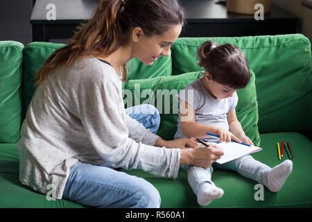 Liebevolle junge Mutter Färbung mit kleinen Tochter - Stockfoto
