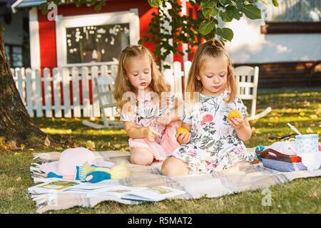 Zwei Mädchen sitzen auf grünem Gras - Stockfoto