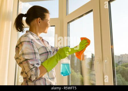 Reife Frau zu Hause waschen der Fenster mit Gummi Schutzhandschuhe mit Feldspritze Waschmittel und Mikrofaser rag - Stockfoto