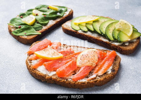 Sandwiches mit Spinat und Avocado Lachs auf einem grauen Tabelle öffnen - Stockfoto