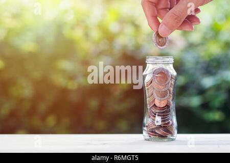 Geldanlage/sparen Geld wachsende Konzept: Hand Münze über Münzen, die in Glas Glas auf Holz Tisch mit Natur und Raum. Konzeptionelle savin - Stockfoto