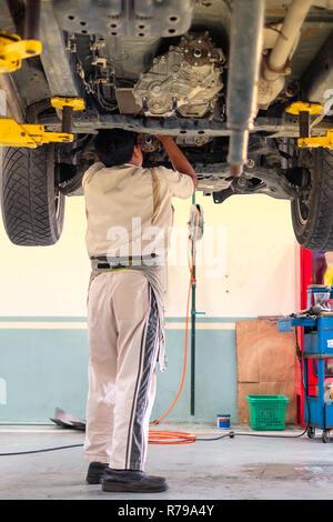 Ein automechaniker stehen unter dem Auto, das ist auf der Hebebühne, Auto Reparatur - Stockfoto