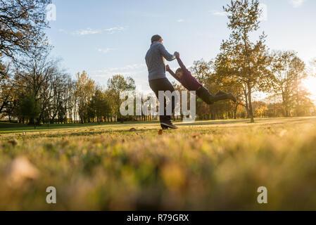 Junger Vater Zeit mit seinem Kleinkind Sohn im Herbst Park holdng ihm seine Hände. - Stockfoto