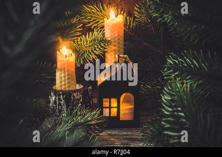 Weihnachten und neues Jahr Spielzeug Haus und zwei Wachs brennende Kerzen unter die Tanne in der Nacht. Weihnachtskarte mit Konzept home Komfort. Urlaub Winter Card. - Stockfoto