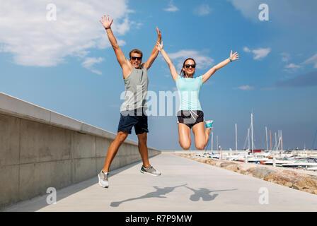 Glückliches Paar in Sport Kleidung springen auf Pier - Stockfoto