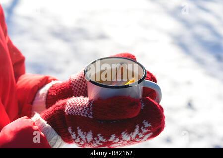 Hände auf Gestrickte Handschuhe Holding dampfende Tasse heißen Tee auf Verschneiten Wintermorgen im Freien. Frau hält Gemütliche festliche rot Tasse mit einem warmen Getränk am Weihnachtsmorgen - Stockfoto