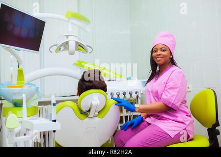 Junge Frau schwarz Arzt in einer Zahnklinik. der Zahnarzt sitzt im Schrank neben dem Stuhl mit der Patienten. Medizintechnik - Stockfoto