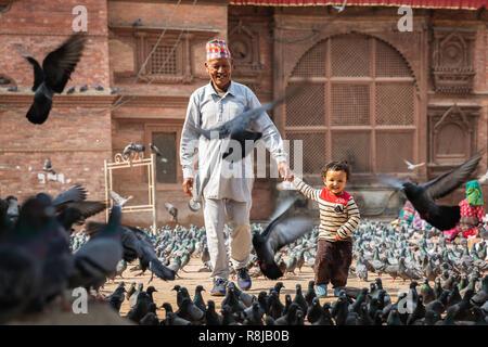 Großvater und Enkel gehen obwohl fliegende Vögel in Durbar Square, ein Weltkulturerbe der Unesco in Kathmandu, Nepal - Stockfoto