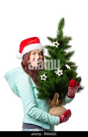 Foto der Frau in Santa's Kappe mit Weihnachtsbaum in der Hand - Stockfoto