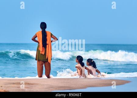 Cochin, Kerala, Indien - 30. November 2017: Mutter und ihre Töchter, zwei indische Mädchen, sitzen am Strand in den Wellen des Ozeans. - Stockfoto