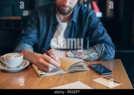 Hand mit Stift schreiben auf Notebook auf einem Holztisch. Close-up - Stockfoto