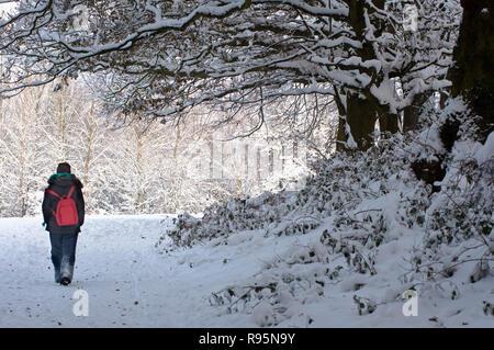 Frau auf einem schneebedeckten Weg in Redditch, Worcestershire. Großbritannien - Stockfoto