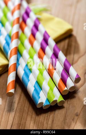 Mehrfarbige Trinkhalme auf hölzernen Tisch gelegt. Lebendige Farben trinken Strohhalme aus Papier. Nahaufnahme Makroaufnahme. - Stockfoto