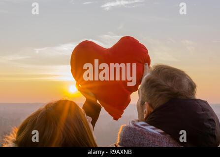 Porträt der jungen romantisches Paar in whit Liebe rotes Herz bei Sonnenuntergang. - Stockfoto