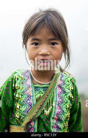 Portrait ein Mädchen von Hmong Ethnizität mit dem traditionellen Gewand auf den Hügeln des schönen Sa Pa in Vietnam. - Stockfoto