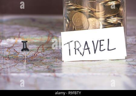 Nahaufnahme von Münzen in ein Glas mit Reisen anmelden und einen Stift auf einer Karte. Konzept der Aufwendungen. - Stockfoto