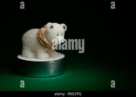 Polar Bear figurine Kerze auf grünem Hintergrund, Inneneinrichtung Konzept - Stockfoto