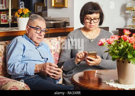 Ehe senior Paar Surfen im Internet mit Handy auf dem Sofa zu Hause sitzen. - Stockfoto